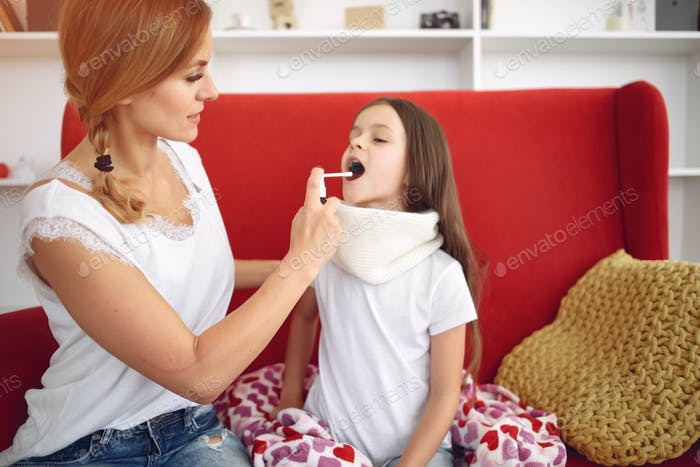 Mutter gibt ihre kranke Tochter Kehle Medizin