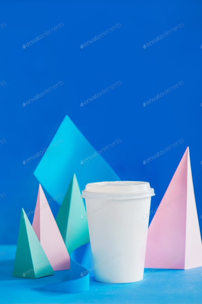 Blank paper cup for coffee on an abstract background with modern paper sculpture. Paper pyramids and