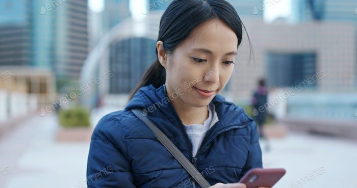 Frau nutzt Handy in der Stadt