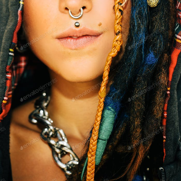 Close-up portrait. Girl with dreadlocks and piercings. Fashionab