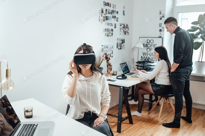 Amazed businesswoman in casual clothing with virtual reality headset
