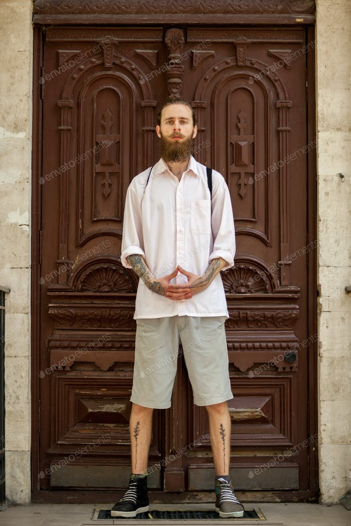 Cool hipster in white shirt posing in front of a door