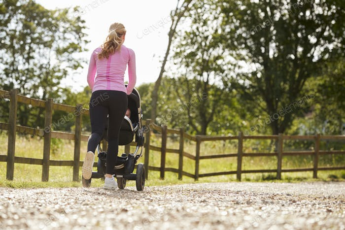 Rear View Of Mother Exercising By Running And Pushing Baby Buggy