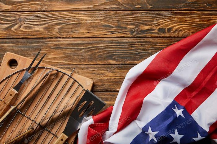 Ansicht der amerikanischen Flagge in der Nähe von BBQ Ausrüstung auf Holz rustikalen Tisch