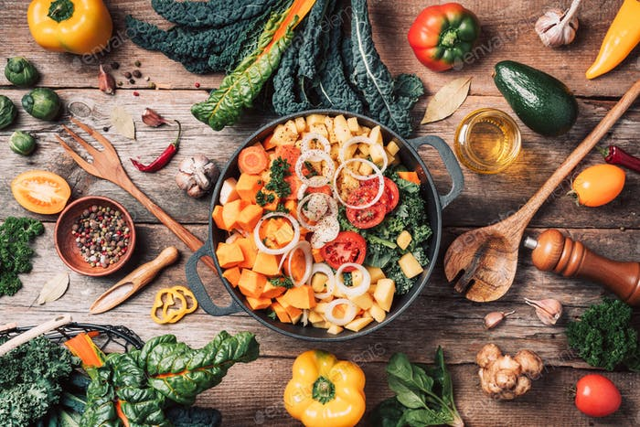 Pot with sliced colorful vegetables and cooking utensils on rustic wooden background. Top view