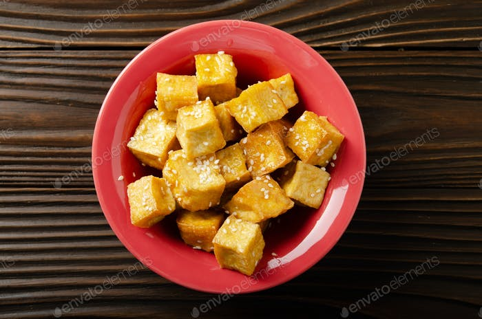 Flat lay closeup view at crispy deep stir fried tofu cubes with chives in clay dish