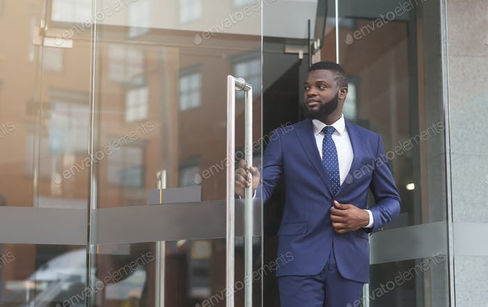 Afro Businessman Talking On Phone Against Office Building Entrance