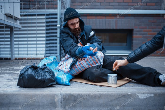 Male bearded beggar begging on city street