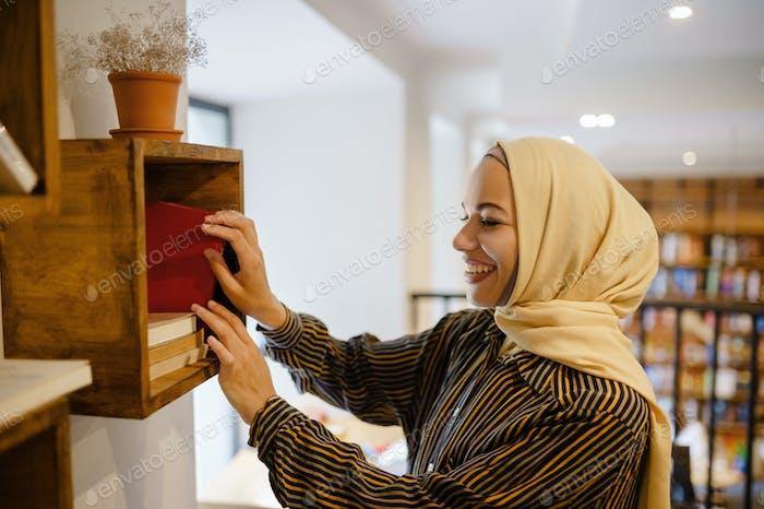 Smiling arab girl in hijab at the bookshelf