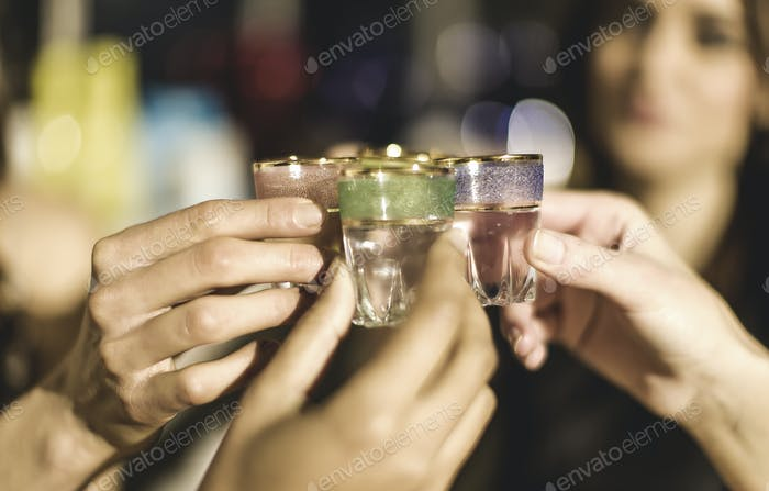A group at a party holding shot glasses and celebrating.