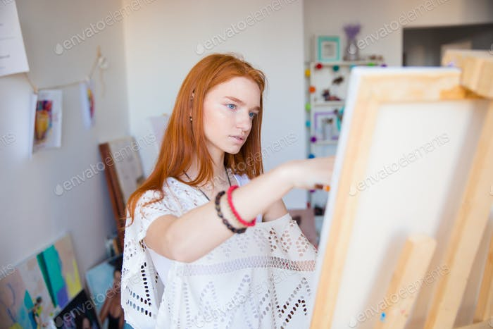 Beautiful pensive young woman painter working in art studio
