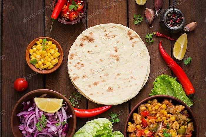 Zutaten für mexikanische Tacos mit Fleisch, Mais und Oliven auf hölzernem Hintergrund. Ansicht von oben