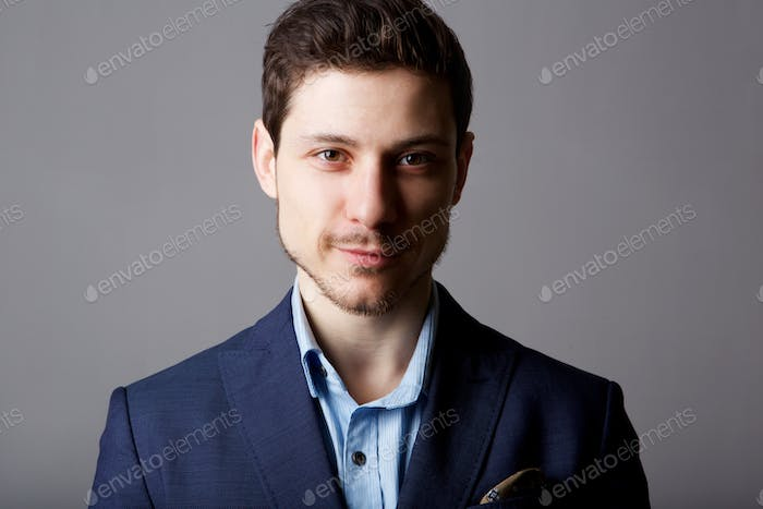 Close up young businessman against gray background