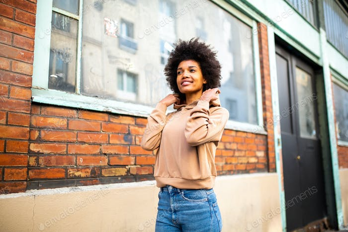 young smiling African american woman walking on street
