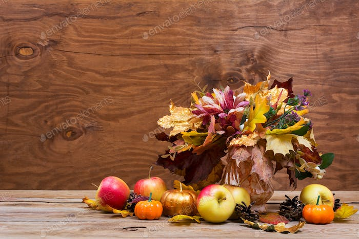 Thanksgiving centerpiece with fall leaves bouquet and apples,