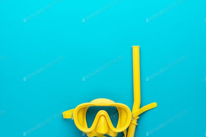 gelbe Tauchermaske und Schnorchel über blauem Hintergrund mit Kopierraum
