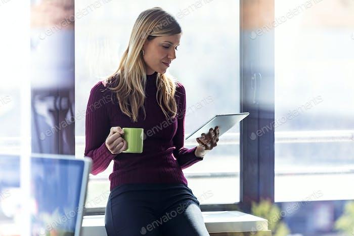 Hübsche junge Geschäftsfrau mit ihrem digitalen Tablet und hält eine Tasse Kaffee im Büro.