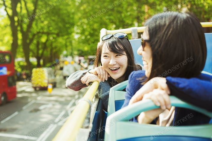 Two smiling women on an open Double-Decker bus tour of London