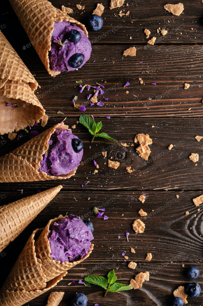 Flat lay view at wafer cones with blackberry icecream on wooden kitchen table