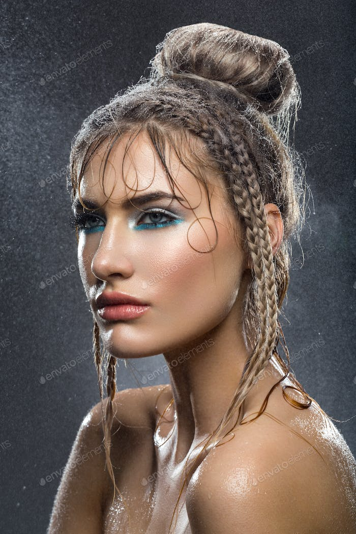 Beautiful girl with blue makeup in water drops
