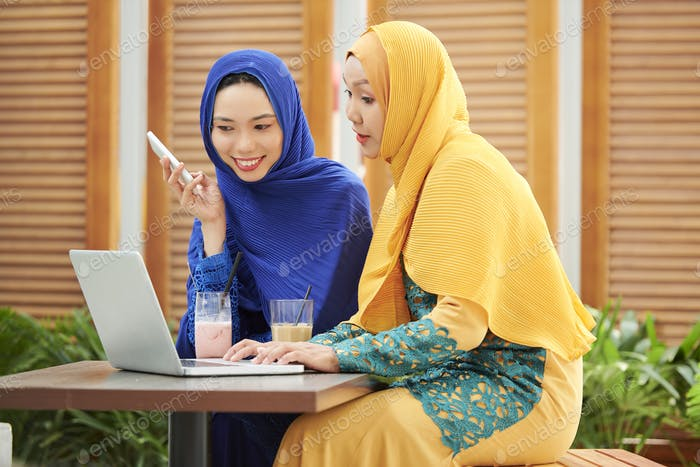 Muslim women discussing project in cafe
