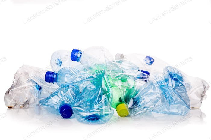 Mineral water bottles crushed and crumpled against white backgro