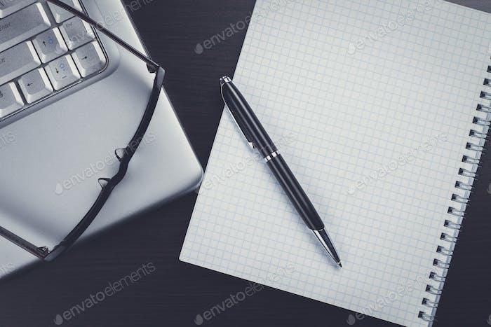 cuaderno en blanco, bolígrafo, gafas y Ordenador portátil en la mesa