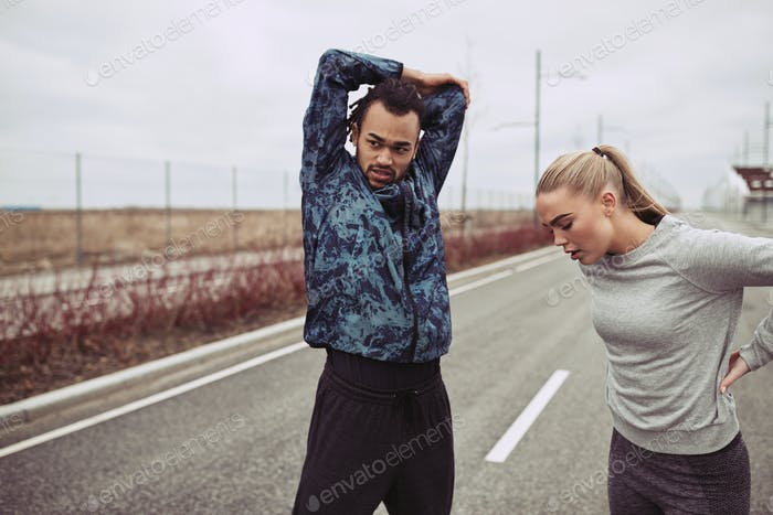 Young couple doing stretches before a run together