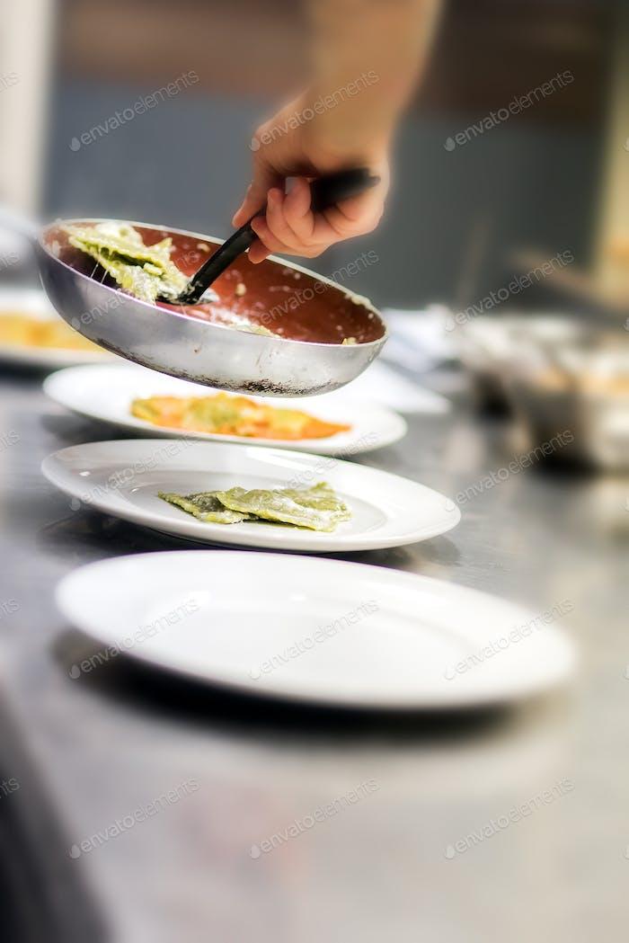 Chef serving ravioli pasta in a restaurant kitchen