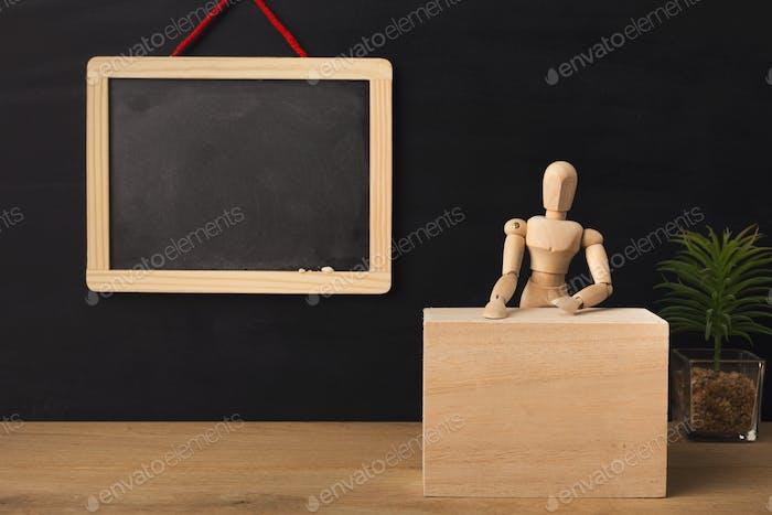 Holzmarionette sitzt im Klassenzimmer