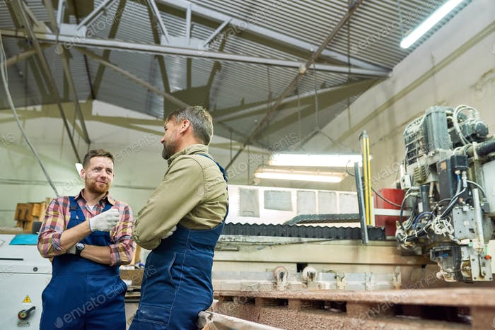 Two Factory Workers Chatting in Workshop