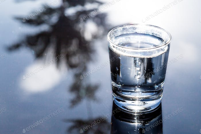 Refreshing water in transparent glass with reflection against bl