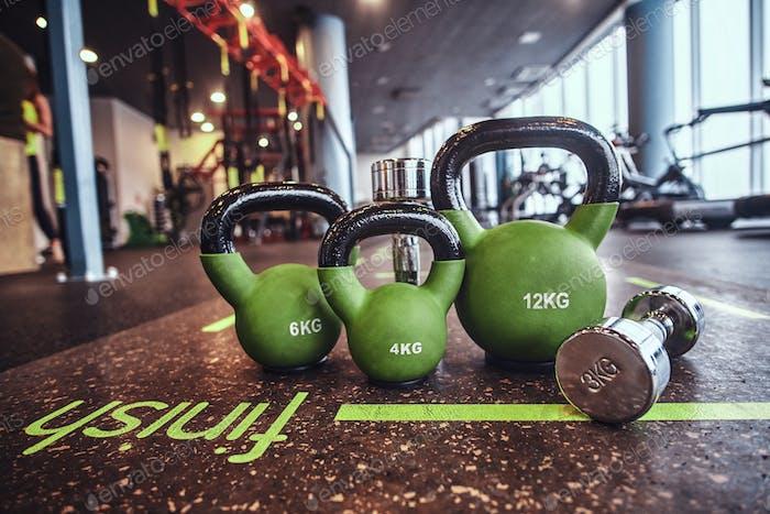 Satz von Gewichten und Hanteln auf der Matte im Fitness-Center.