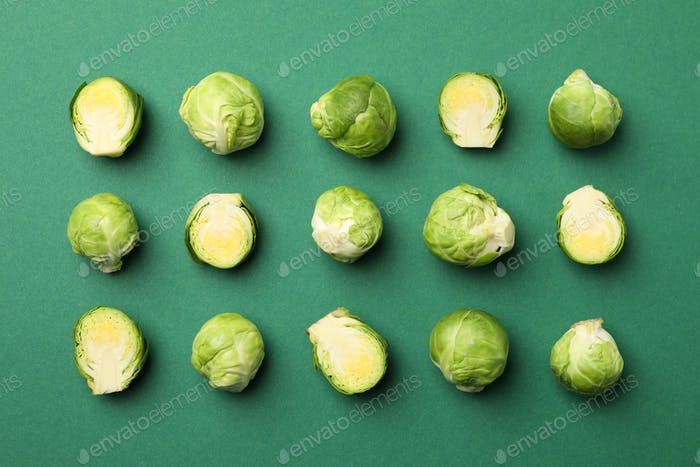 Flat lay with brussels sprout on green background, top view