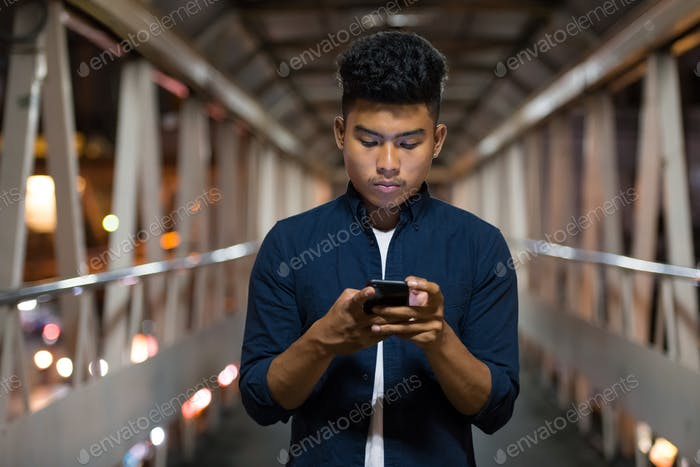 Young Asian man using phone on the footbridge at night