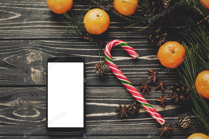 Candy andphone with white blank screen and tangerines