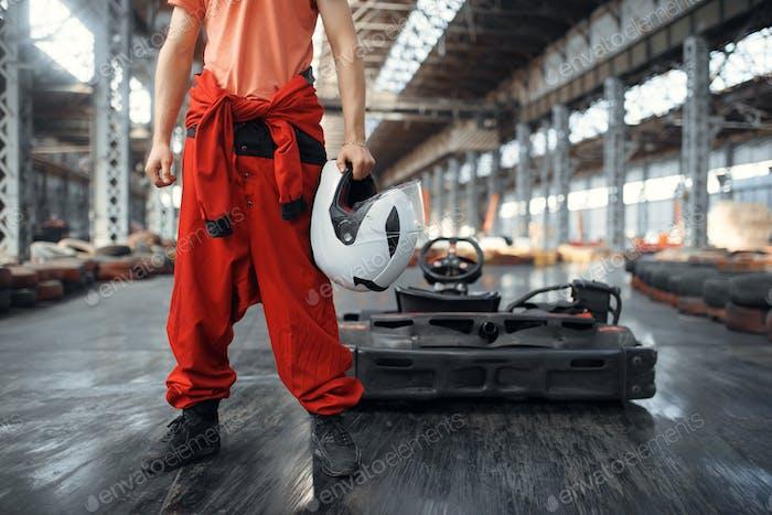Racer with helmet, go kart car on background