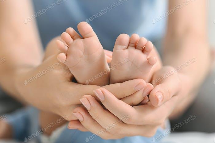Newborn baby feet in mother's hands closeup