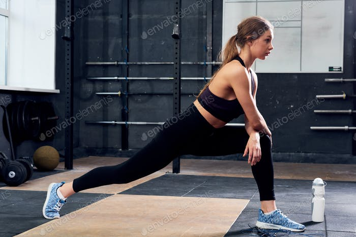 Beautiful Young Woman Stretching in CrossFit Gym