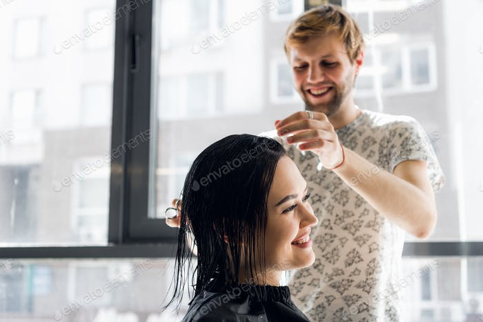 Laughing girl and hairdresser talking and smiling while making a new haircut or hairstyle