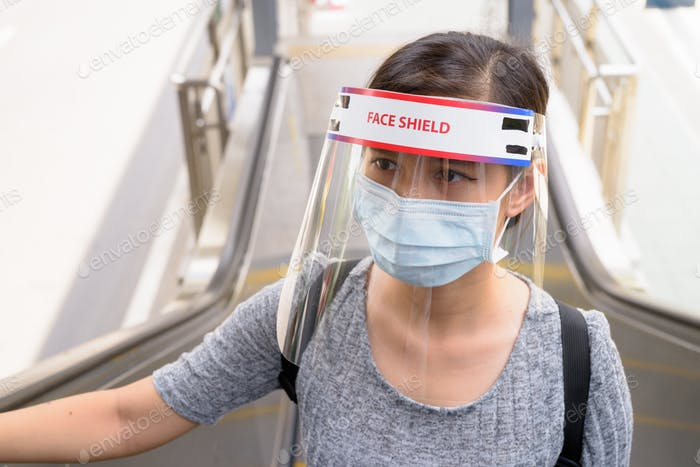 Young Asian woman with mask and face shield moving up the escalator