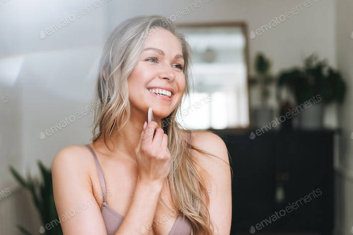 Blonde smiling woman 35 year  with long hair does facial massage with gouache scraper