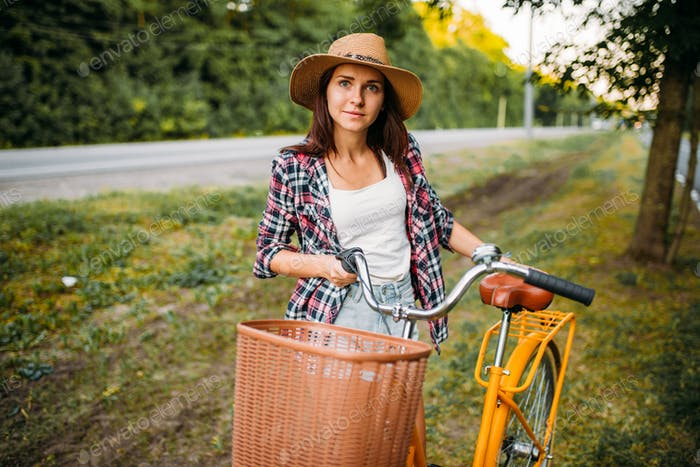 Woman in hat against vintage bicycle with basket