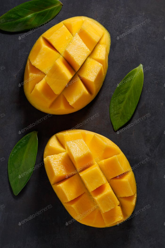 The two halves of ripe mango on the black textured table. View from above.