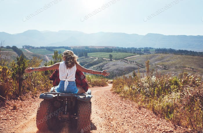 Couple having fun on a quad bike in countryside