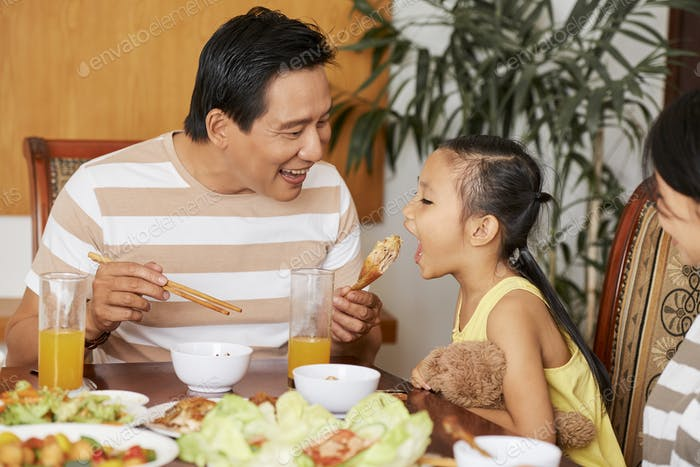 Lovely father eating together with daughter