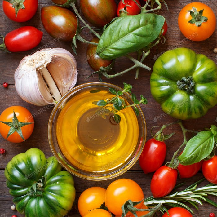Colorful tomatoes, garlic, olive oil and herbs