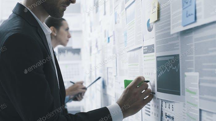Geschäftsleute überprüfen Finanzberichte an einer Wand