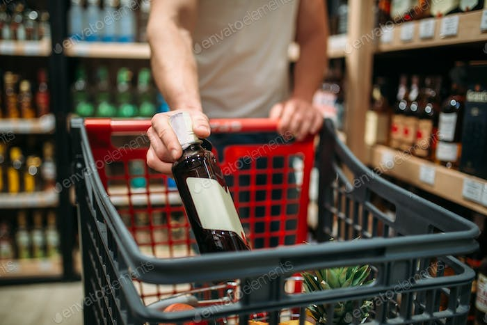 Male person put bottle of wine in a cart