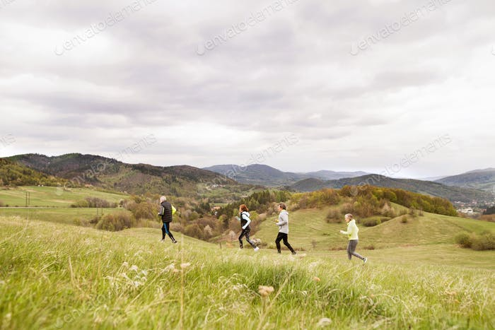 Group of seniors running outside on the green hills.